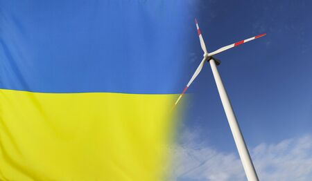 merged: Concept clean energy with flag of Ukraine merged with wind turbine in a blue sunny sky