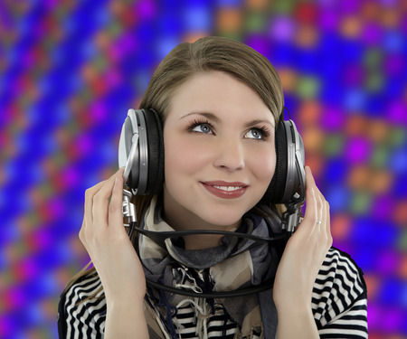 Beautiful young smiling woman listens to music with headphones on her head concept with colorful  background photo