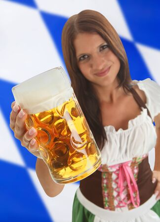 Bavarian Woman in traditional dirndl clothing  holding Oktoberfest Beer with a bavarian flag in the background Stock Photo