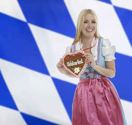 pinafore: Smiling bavarian woman in traditional clothing with an Oktoberfest Gingerbread heart with a bavarian flag in the background
