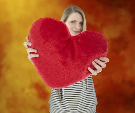 Young beautiful woman showing a red heart shaped pillow with a orange and red aquarell painted background photo