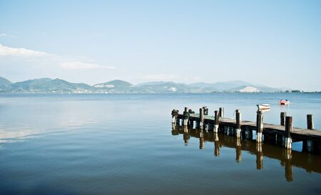 puccini lake with dock and boat in the distance Stock Photo