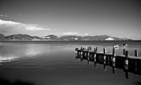 puccini's dock on the lake in black and white Stock Photo