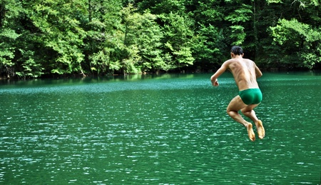 young boy dives into the lake