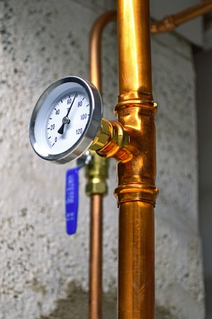 Hot water thermometer on a water pipe photo