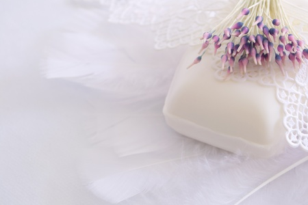 Soap embedded in white feathers, lace and artificial flower photo