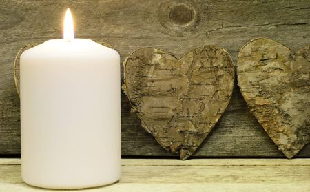 Burning candle with wooden background and bark heart photo