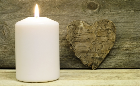 white candle: Burning candle with wooden background and bark heart