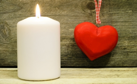 One white candle and red wooden heart still life photo