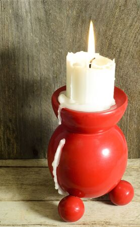 Red and round traditional candle holder with burning candle photo