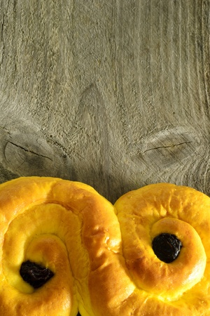 Sweet saffron bun with wooden background, rustic Stock Photo - 17076367