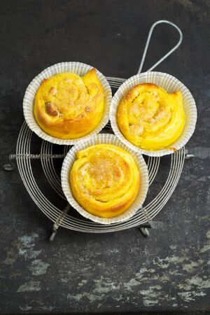 Homemade saffron buns with almond paste filling on a baking tray and trivet photo