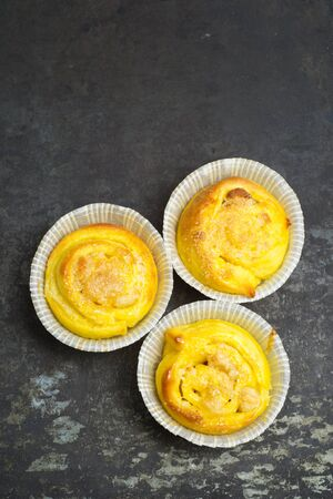 Homemade saffron buns with almond paste filling on a baking tray photo