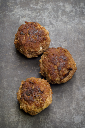 Three fried meatballs on a baking tray, rustic style photo