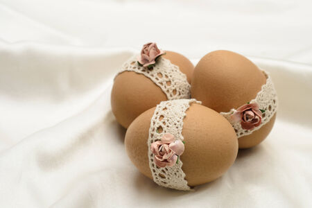 silken: Decorated Easter eggs with lace and artificial flowers on silken background