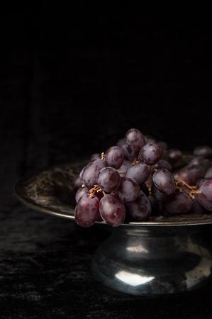 black velvet: Purple Grapes still life, vintage fruit bowl, black velvet background.