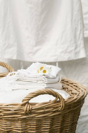 daisie: Basket full of clean freshly washed grandmothers linens. Outdoor, laundry hanging background. Stock Photo