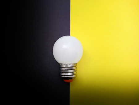 Light Bulb Simulating On and Off on Colored Paper Stock Photo