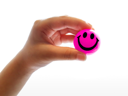 The Bright Pink Smiley Ball in the Hand of a Child