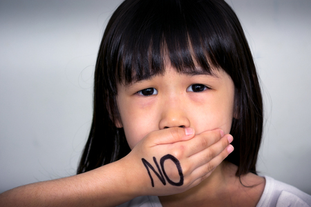 Child Covering her Mouth with No Written Over the Hand