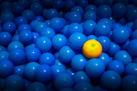 feast: A Fruit Orange in a Sea of Blue Bouncy Plastic Balls Stock Photo