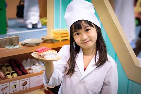 Asiatisches Mädchen Rollenspiel als Sushi-Chef Standard-Bild