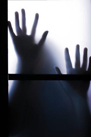 Spooky Pair of Blurred Hands through a Frosted Glass Window