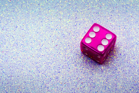 A Metallic Pink Lucky Role of Six on a Christmas Themed Dice