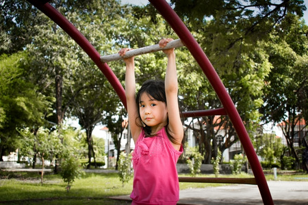 Asian Little Girl Hanging on Monkey Bars in a Park