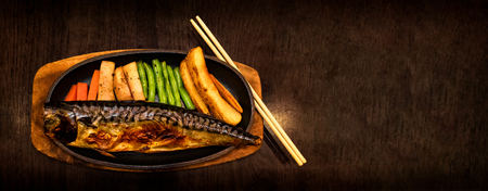 Japanese Styled Mackerel Fish Steak Served on a Hot Plate with Side Dish of French Fries, Celery and Mushrooms Banco de Imagens