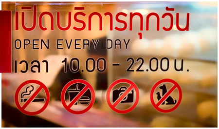 Thai Characters that translates to Open Everyday and Restriction Signs on the Glass of a Local Restaurant Banco de Imagens