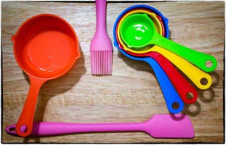 Set of Colorful Measuring Spoon, pink Spatula and Brush on a Wooden Background Banco de Imagens