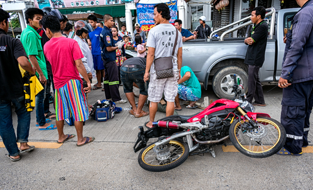 BANGKOK, THAILAND - OCTOBER 14: Rescue Workers get to work to assist a man in a motorcycle traffic accident while surrounded by onlookers in Bangkok on October 14, 2017.
