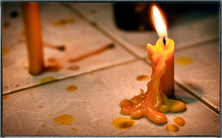 Melted Wax from a Yellow Lighted Candle in the Evening