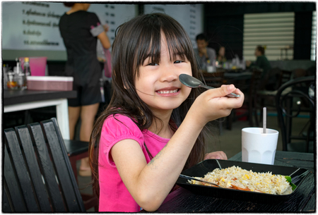 Child Eats Fried Rice with a Spoon in a Authentic Asian Restaurant Banco de Imagens