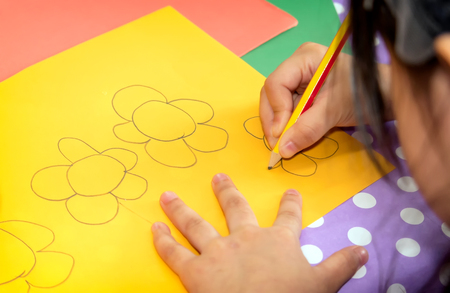 Child Draws Flowers on a Piece of Colored Paper with a Pencil Banco de Imagens