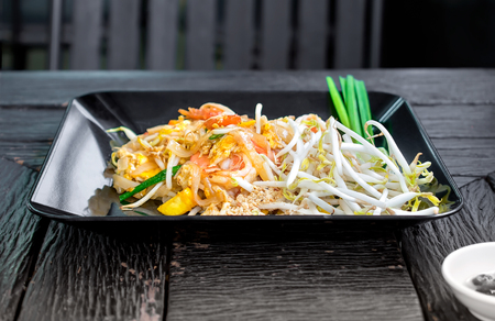 Dish of Thai styled Pan Fried Noodles, Pad Thai on a wooden background