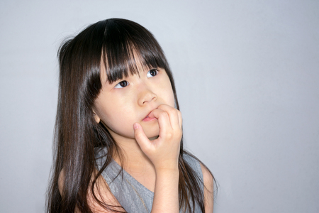 Asian Little Girl with Confused and Frustrated when faced with a Dilemma Banco de Imagens