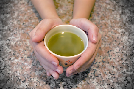 Cup of Hot Japanese Green Tea in the Palms of both Hands