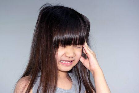 Asian Little Girl with Reaction to a Splitting Headache Stock fotó