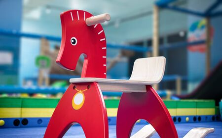 Red Wooden Rocking Horse in a Indoor Playground