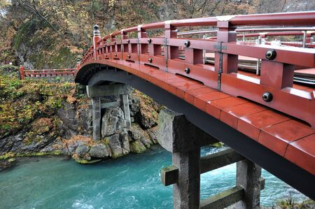 Japan red bridge with flowing river underneath