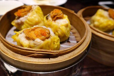Chinese Dim Sum, Pork Meat Dumplings (Siu Mai) With Abalone in a bamboo basket