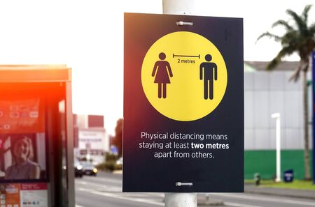 Covid-19 warning sign on a pole urging people to keep physical distancing 2 metres apart from others