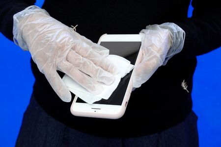 Coronavirus prevention cleaning, A young woman disinfects her smartphone with wet wipes and disinfectant. 版權商用圖片