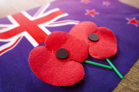 Close up on Remembrance poppies on a New Zealand flag.