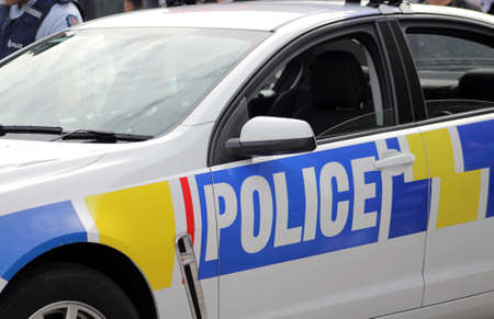 Close up New Zealand police car with policeman on background