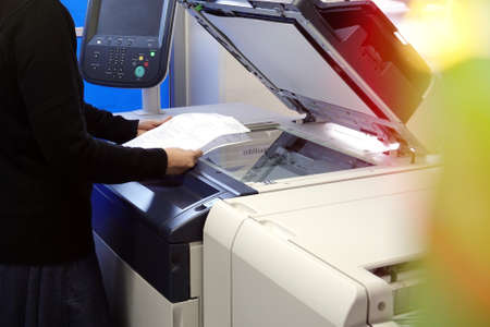 Young woman making photocopies on a copy machine in office.