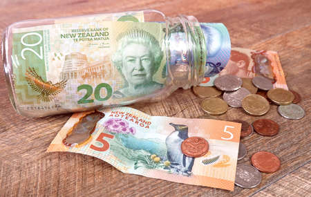 Saving money concept, New Zealand currency in glass jar on wooden background. 免版税图像 - 154257952