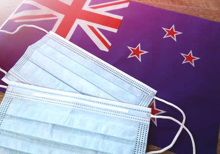 Coronavirus and Economic Crisis, Close up face mask on New Zealand flag